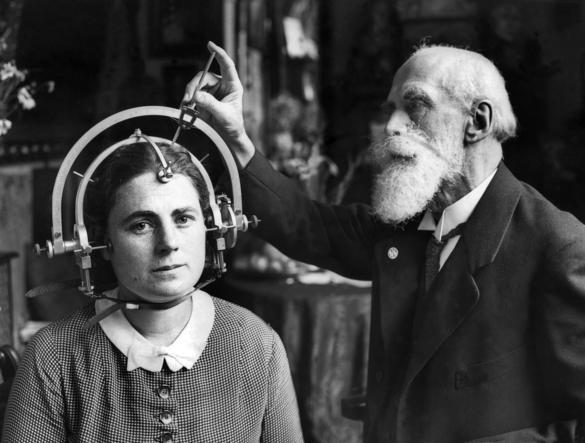 Bilden föreställer en person som mäter en annan persons skalle med verktyg