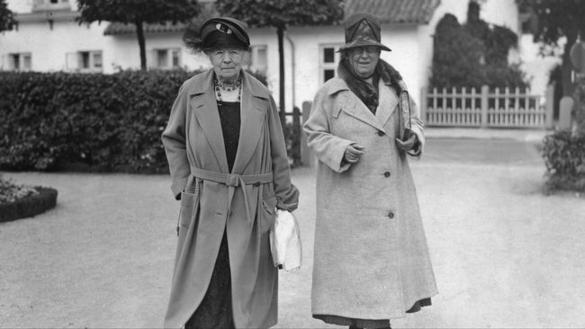 Bilden visar två äldre kvinnor som står bredvid varandra utomhus.