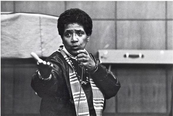 Bilden visar en kvinna som ser upprörd ut och talar i en mikrofon.