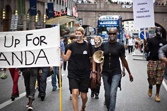 Bilden visar deltagare i prideparaden som bär på skyltar med budskap om Uganda och HBTQ-rättigheter