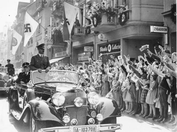 Adolf Hitler ståendes i en bil längs en gata full med folk i Bonn, Tyskland, 1938.