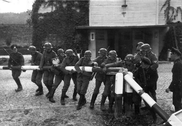Svartvit bild på tyska soldater som tar bort bommen vid gränsen till Polen.