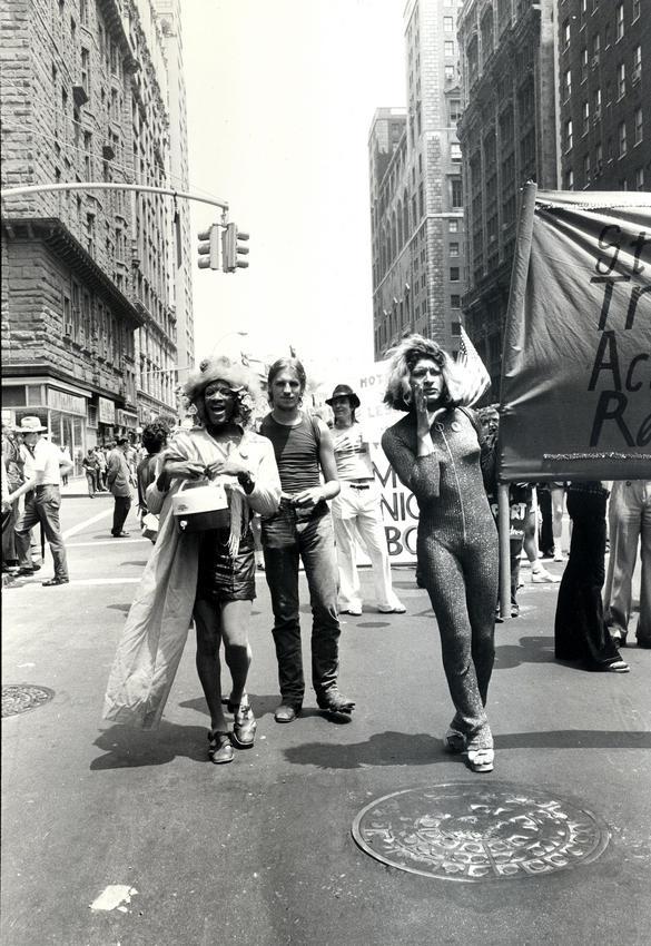 Bilden visar människor som går i en demonstration och håller upp en banderoll.