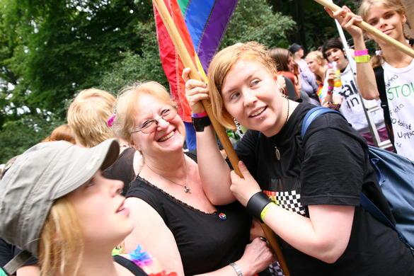 Bilden visar personer på en demonstration med en regnbågsflagga.