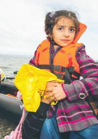 Bilden visar en flicka med flytväst på en strand.
