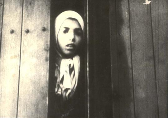 Bild på flicka med sjalett i en tågvagn.