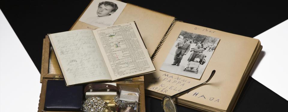 Bilden visar ett uppslaget gammalt fotoalbum, en anteckningsbok, ett smyckesskrin samt del av glasögonbåge.