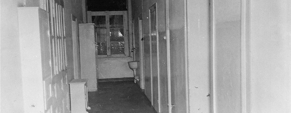 Bilden visar en tom och ödslig korridor med flera dörrar.
