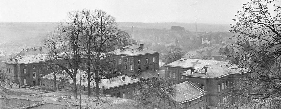 Bilden är ett svart-vitt foto på flera större byggnader taget på avstånd.