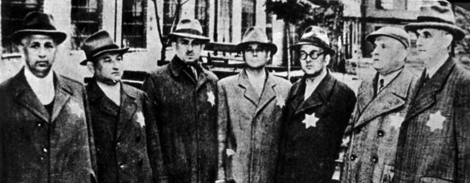 Bilden visar ett svartvitt fotografi av sju män på rad med gula stjärnor på sina rockar.