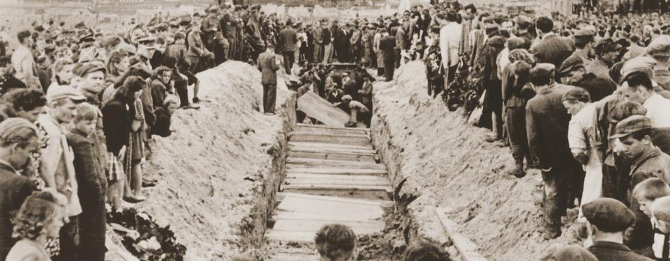 Bilden visar en lång rad av kistor omringad av en stor folkmassa.