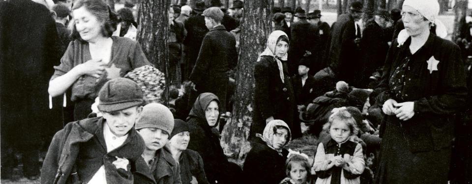 Bilden visar kvinnor och barn som står i en skogsdunge.