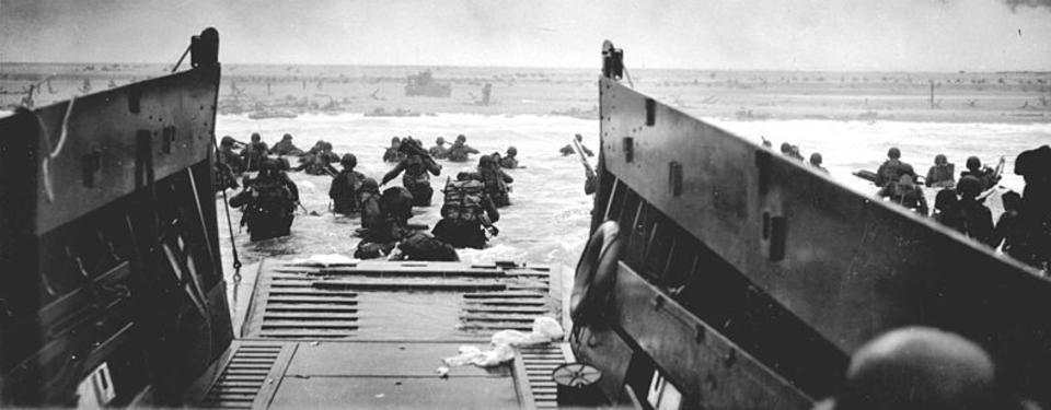 Bilden visar båt med bryggan nedfälld i vattnet och soldater vadandes mot stranden.