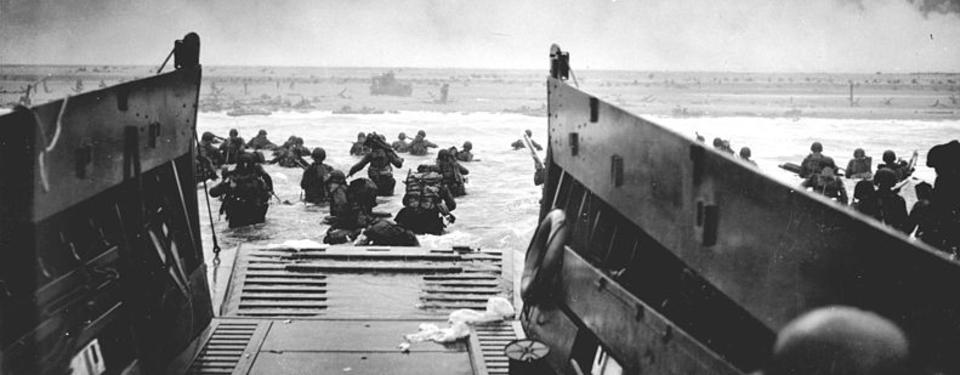 Bilden visar båt med brygga utfälld och beväpnade soldater med ryggsäck vadandes mot land.