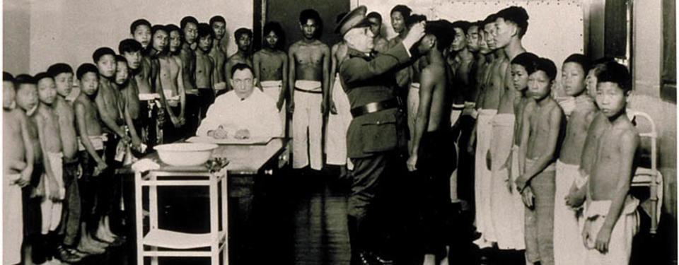Bilden visar många yngre pojkar ståendes i uform, en man i vit rock sittandes vid bord med balja mitt bland pjokarna samt en uniformsklädd man tittandes på en av pojkarna.