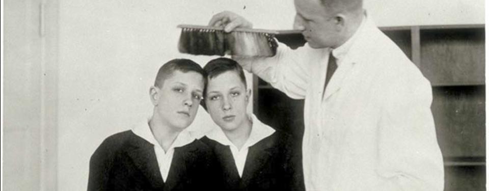 Bilden visar två pojkar sittandes bredvid varandra och en stående man i vit rock hållandes någonting över pojkarnas huvud.