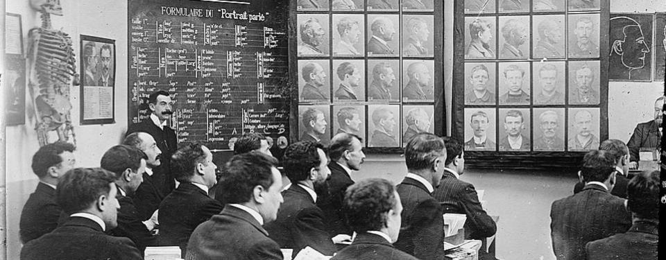 Bilden visar ett rum med en man längst fram vid ett skrivbord och andra män sittandes framför. På väggarna porträtt, text och ett skelett.