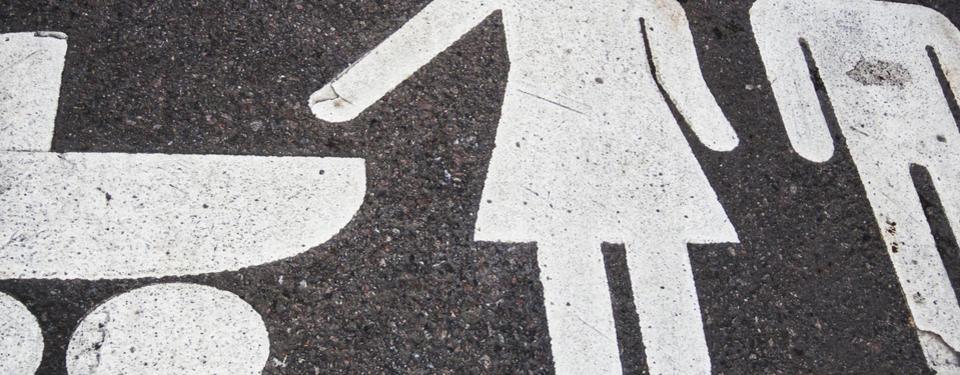Bilden visar vit målning på asfalt av man, kvinna och barnvagn.