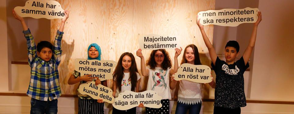 Bilden visar barn/elever som håller upp skyltar med demokratiska budskap.