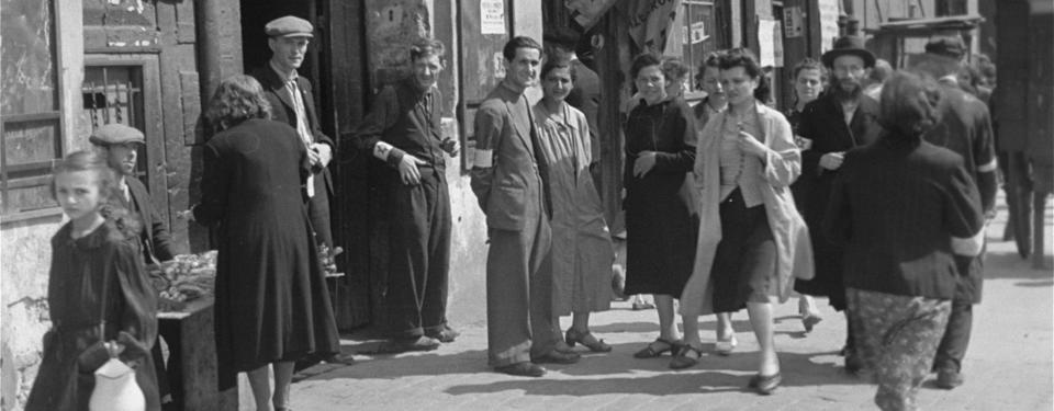 Bilden visar människor ståendes och gåendes på en gata, många med vit armbindel med davidsstjärna på armen.