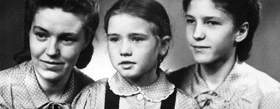 På bilden syns tre sittande personer I närbild. Else Schmidt med hennes två styvsystrar. Else syns i mitten av bilden, på sidorna syns styvsystrarna som är äldre än Else. Alla tre är klädda i prickiga blusar.