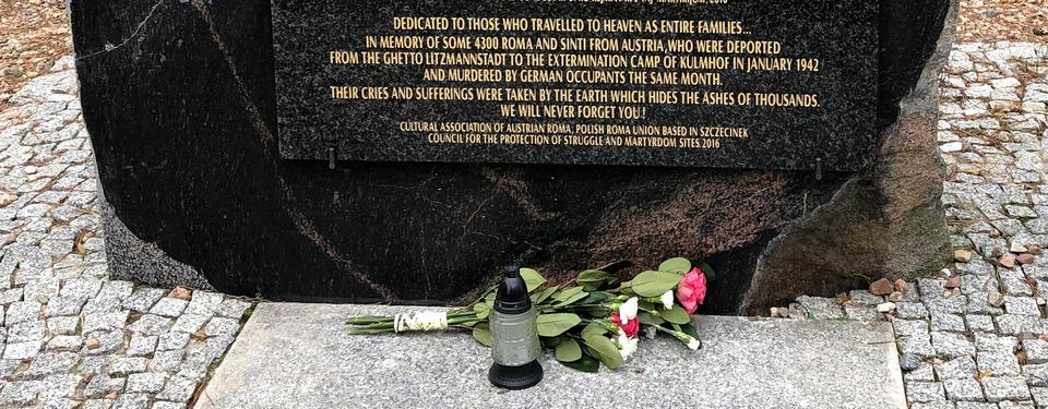 Bilden visar ett minnesmärke i form av en stor svart sten.