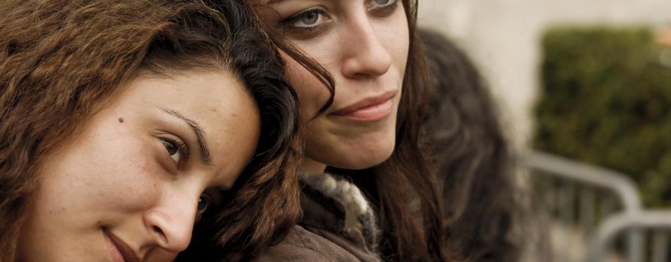Bilden visar en närbild på två unga kvinnor, den ena lutandes huvudet mot den andras axel.
