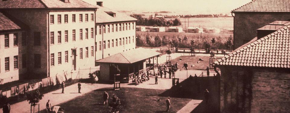 Bilden visar en stor byggnad med gräsplätt i mitten och människor.