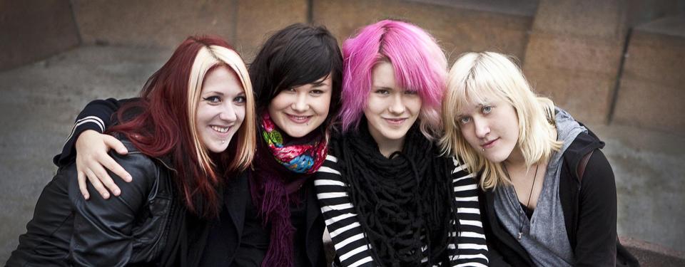 Bilden visar fyra tjejer sittandes nära varandra.