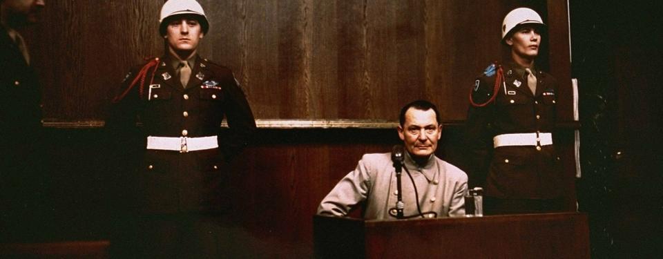 Bilden visar en man sittandes i ett vittnesbås och två uniformerande män ståendes i bakgrunden.