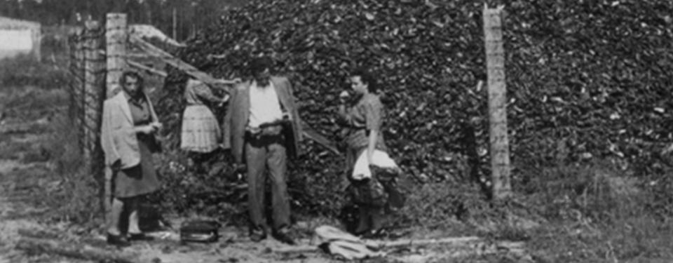Bilden visar mängder av skor, nästan dubbelt så hög som mannen som står framför dem.
