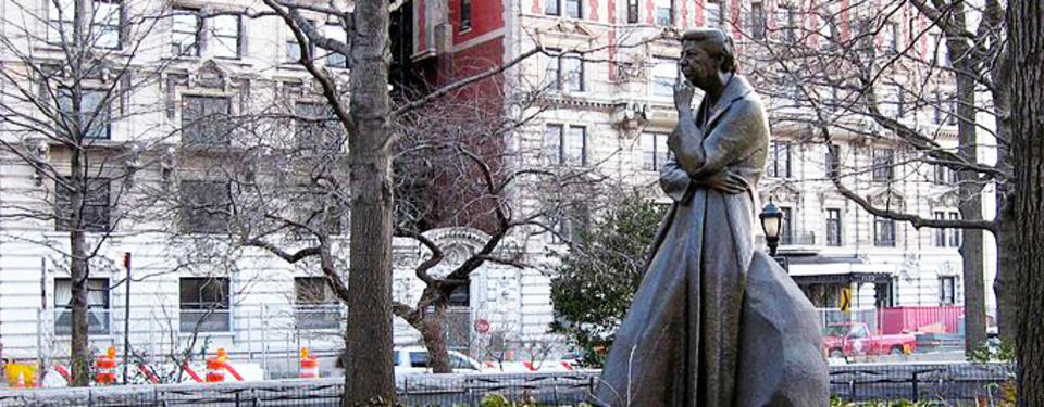 Bilden visar en staty av en kvinna i klänning och kappa.