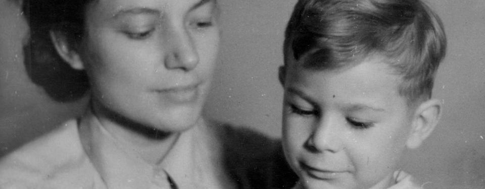 Bilden är en porträttbild tagen i fotostudio på en kvinna och en pojke i 5-7 årsåldern. Kvinnan tittar på pojken och ler lite.