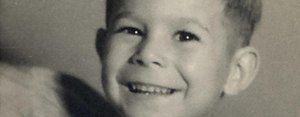 Bilden är en porträttbild tagen i fotostudio på en ung pojke som ler mot kameran.