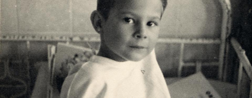 Bilden visar en ung pojke som sitter upp i en sjukhussäng och tittar in i kameran. Det är en äldre säng med stålram och i den finns ett papper och en penna.