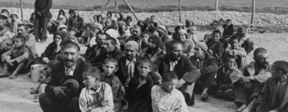 Bilden visar ett femtiotal män, kvinnor och barn sittandes på marken.