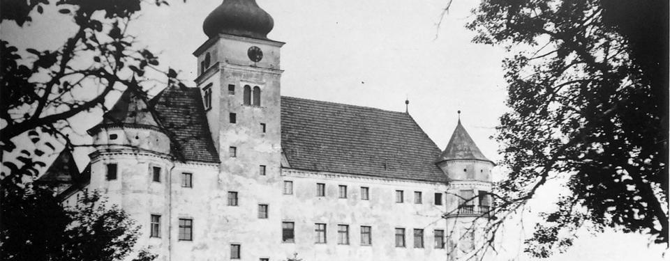 Bilden visar en stor vit byggnad med torn i varje hörn.