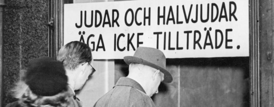 Bild av människor framför ett skyltfönster med texten: Judar och halvjudar äga icke tillträde.