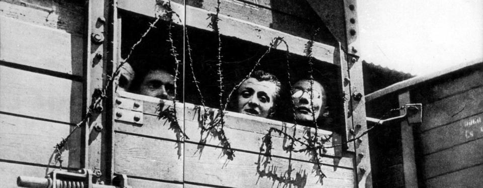 Bilden visar tre män som tittar ut ur en boskapsvagn.