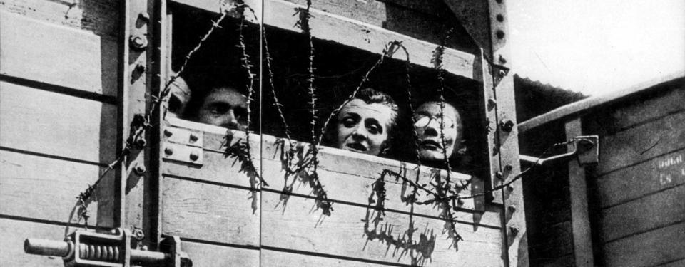 Bilden visar tre mäns ansikten i taggtrådstäckt öppning i trävagn.