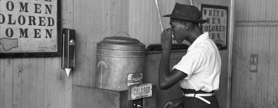 En man dricker vatten från en vattenfontän märkt med texten