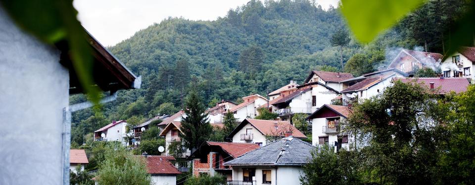 Bilden visar små hus byggda på sluttning och en skogsbeklädd höjd i bakgrunden.