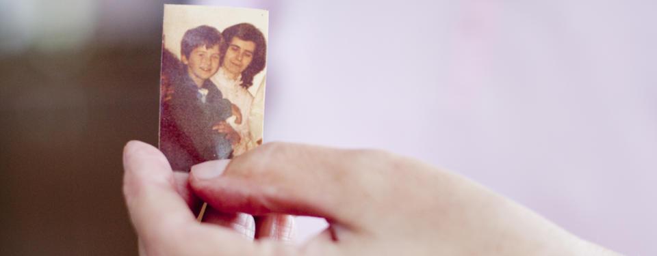 Bilden visar en hand hållandes ett foto på en kvinna och ett barn.