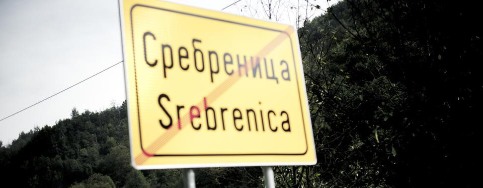 Bilden visar en skylt med texten Srebrenica och ett rött sträck diagonalt över skylten.
