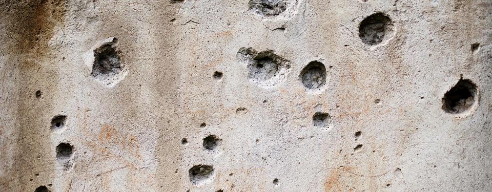 Bilden visar närbild på betongvägg med hål i.