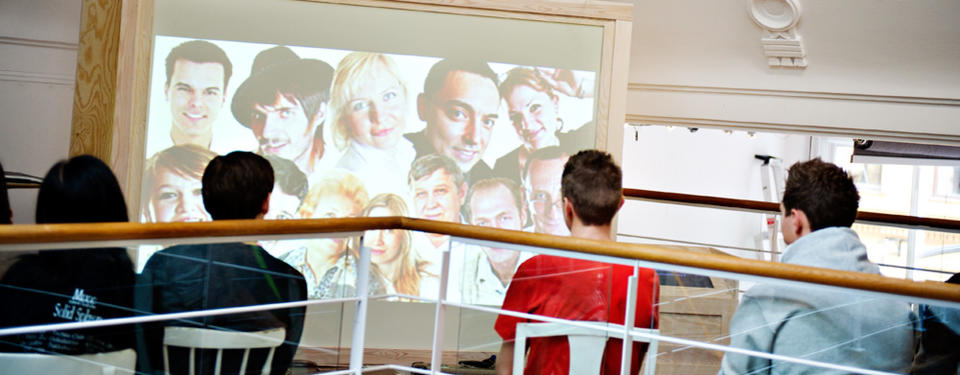 The image shows four students watching a screen that shows portraits.