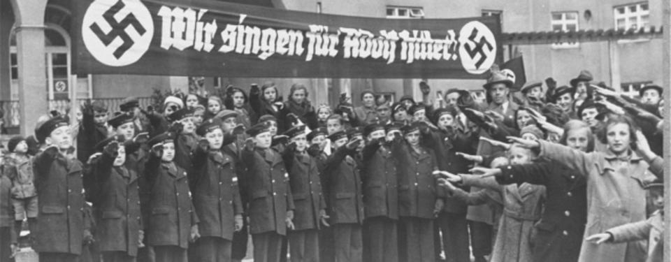 Bilden visar uniformsklädda, hitlerhälsande ungdomar under banderoll med texten wir singen für Adolf Hitler. Vid sidan, civilklädda hitlerhälsande ungdomar.