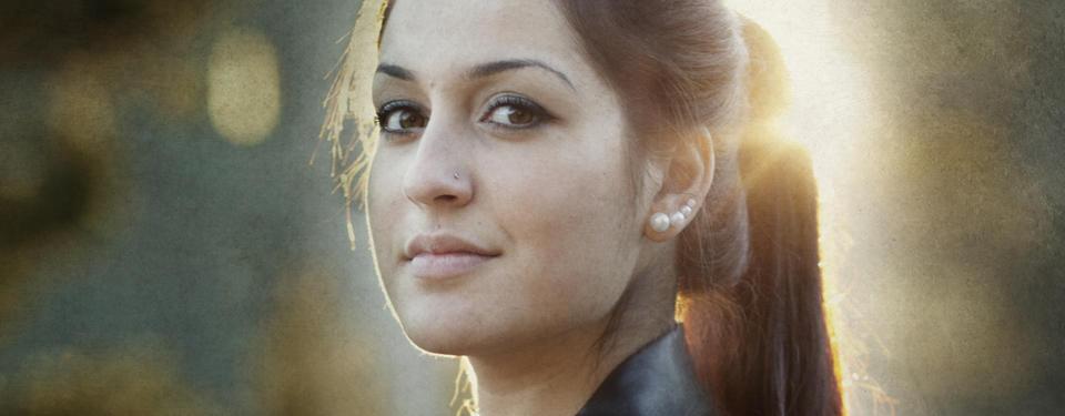 Bilden visar ett porträtt av en ung tjej i mörkt hår som tittar in i kameran.