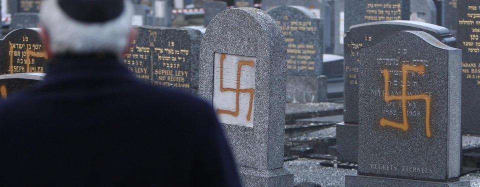 Bilden visar en man framför gravstenar vandaliserade med hakkors.