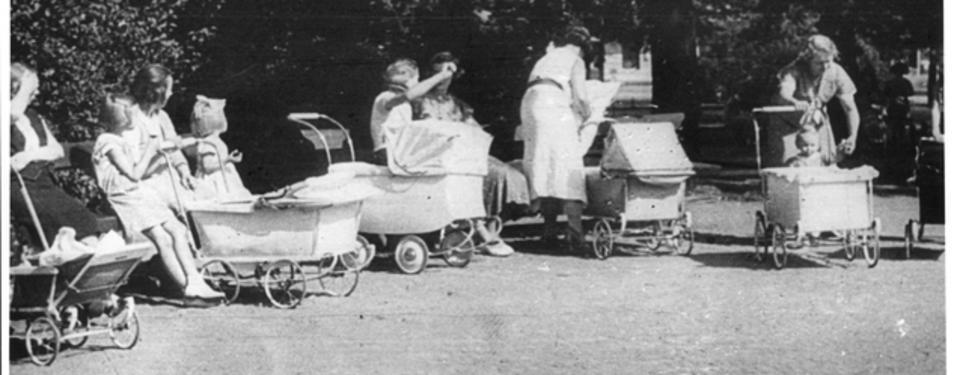 Bilden visar fem barnvagnar i en park med kvinnor och barn i närheten.